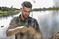 Man preparing fishing rod next to pond - ZEF010202