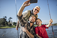 Grandfather, father and son taking a selfie with fishing rods - ZEF010229