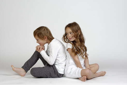 Boy sitting back to back on ground with his little sister - LBF001464