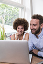 Young woman and man using laptop at the window - WESTF021654