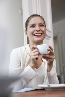 Smiling young woman with cup of coffee - WESTF021669