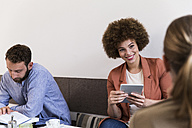 Smiling young woman with tablet in a cafe looking at woman - WESTF021675