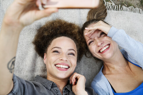 Two happy young women taking a selfie on blanket - WESTF021747