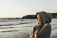 France, Crozon peninsula, woman wearing a cardigan on the beach at sunset - UUF008329