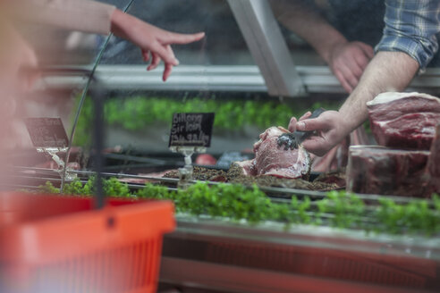 Client choosing meat from butchery display - ZEF010286