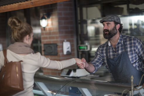 Butcher shaking hands with client in butchery - ZEF010292