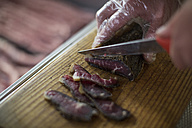 Butcher cutting biltong on wooden board - ZEF010301