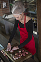 Woman working in a butchery rolling bacon meat rolls - ZEF010304
