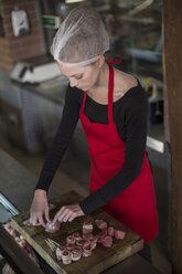 Woman working in a butchery rolling bacon meat rolls - ZEF010304