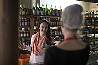 Smiling woman in shop talking to shop assistant - ZEF010307
