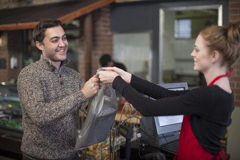 Shop assistant handing over bag to customer in shop - ZEF010310