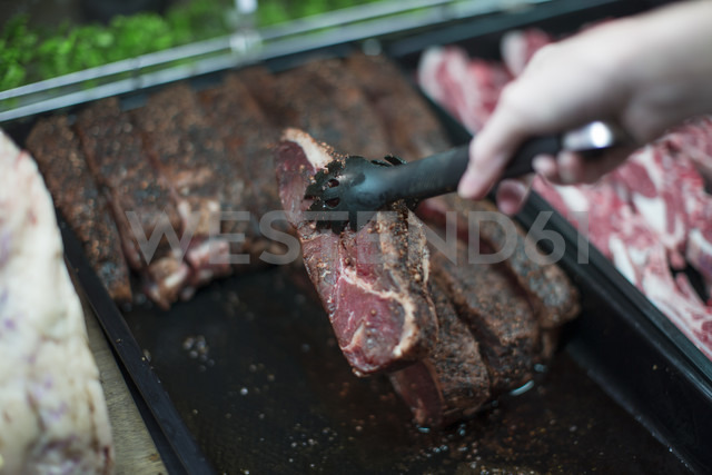 Hand taking meat from display in butchery - ZEF010313