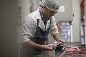Butcher packing raw meat in butchery - ZEF010316
