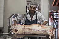 Butcher cutting carcass with bandsaw in butchery - ZEF010322