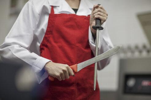 Butcher sharpening his knife - ZEF010334