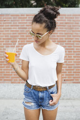 Young woman holding orange juice outdoors - MRAF000156