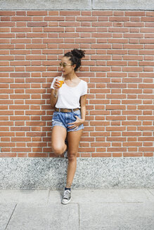 Young woman leaning against a brick wall drinking orange juice - MRAF000159