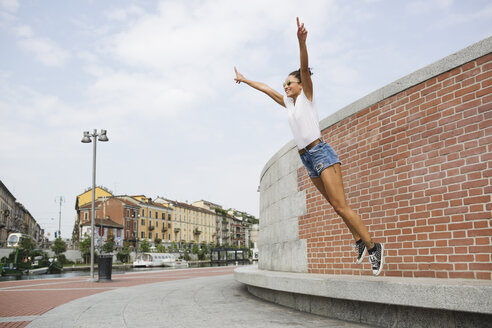 Exuberant young woman jumping outdoors - MRAF000168