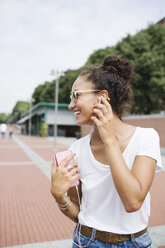 Happy young woman listening to music outdoors - MRAF000174