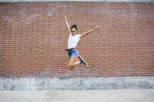 Exuberant young woman jumping  in front of a brick wall - MRAF000177
