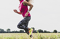 Young woman running in rural landscape - UUF008359