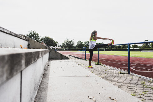 Young woman stretching in a track and field stadium - UUF008368