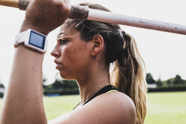 Young woman with smartwatch holding javelin - UUF008374