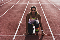 Young woman on tartan track in starting position - UUF008380