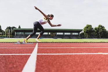 Young woman on tartan track starting - UUF008383