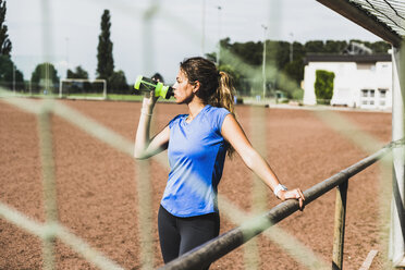Sportive young woman standing on sports field drinking from bottle - UUF008389