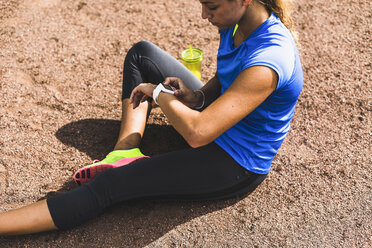 Sportive young woman sitting on sports field drinking looking at smartwatch - UUF008392