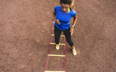 Young woman exercising on sports field with agility ladder - UUF008395