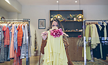 Woman holding dress in a boutique - DAPF000315