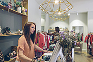 Shop assistant at counter in a boutique - DAPF000324