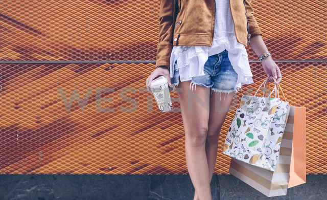 Low section of woman holding shopping bags and takeaway coffee - DAPF000333