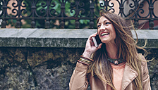 Happy woman on cell phone outdoors - DAPF000336