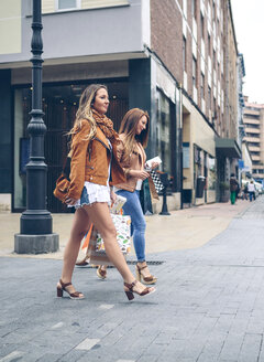 Two women holding shopping bags walking in the city - DAPF000339