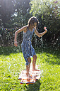 Girl having fun with inflatable water cushion in the garden - SARF002862