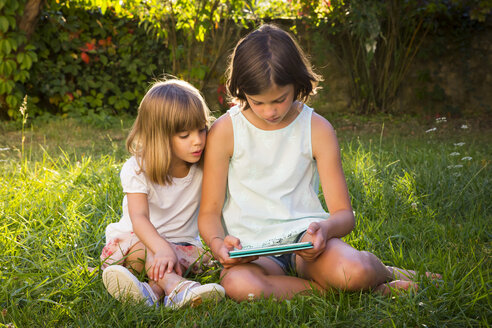 Two little sisters sitting on a meadow looking at tablet - LVF005276