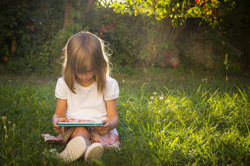 Little girl sitting on a meadow looking at tablet - LVF005282