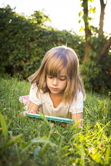 Little girl lying on a meadow using tablet - LVF005285