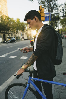 Teenager with a bike in the city, using smartphone - EBSF001725