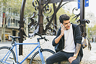 Teenager with a bike in the city, using smartphone - EBSF001740