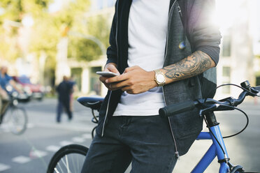 Teenager with a fixie bike, using smartphone - EBSF001743