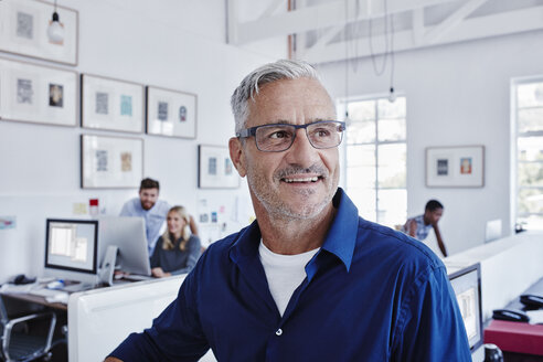 Smiling businessman in office with staff in background - RORF00287