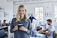 Portrait of smiling businesswoman in office with staff in background - RORF00290