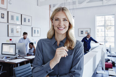 Portrait of smiling businesswoman in office with staff in background - RORF00293