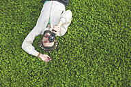 Young man lying on a meadow using a vintage video camera - RTBF00349