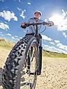France, Brittany, senior man on electric mountainbike on coastal trail - LAF01718