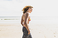 Teenage girl walking on the beach - UUF08396